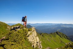 Backpacker standing on a rock over the cliff Royalty Free Stock Photos