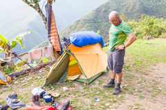 Backpacker standing tent morning mess gear disorder, camping mou Stock Photos
