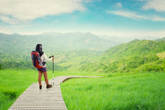 Backpacker with stick on the wooden path Royalty Free Stock Photo