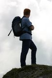 Backpacker on the summit. Hillwalker silhouetted against sky Royalty Free Stock Photography
