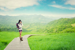 Backpacker taking picture on the wooden path Royalty Free Stock Images