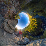 Backpacker on top of a rock fall at dawn. spherical degree panorama 360 180 little planet.  Stock Photo