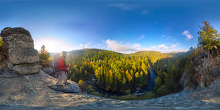 Backpacker on top of a rock fall at dawn. Spherical panorama 360 180 degrees equidistant.  Stock Image