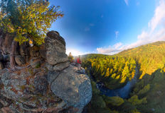 Backpacker on top of a rock fall at dawn. Wide angle aerial panorama Stock Images