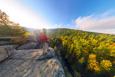 Backpacker on top of a rock fall at dawn. Wide angle aerial panorama.  Stock Photography