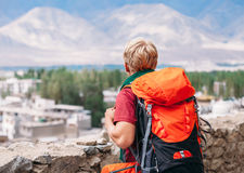 Backpacker tourist looks on blue mountain Royalty Free Stock Photography