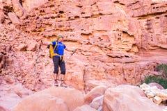 Backpacker tourist man standing desert stone canyon mountain trail Stock Photography