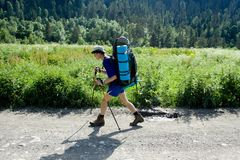 Backpacker tourist on the road. Royalty Free Stock Photo