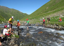 Backpacker tourists crossing river stock image