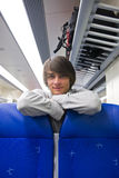 Backpacker in train. Backpacker leaning over the head rests of a couple of seats in a train, with his backpack on the luggage rack above him Stock Photo