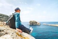 Backpacker traveler relax on rocky coast of blue sea lagoon. Backpacker traveler relax on the rocky coast of blue sea lagoon Royalty Free Stock Photos