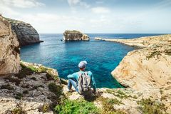 Backpacker traveler relax on the rocky coast of blue sea lagoon Royalty Free Stock Photo