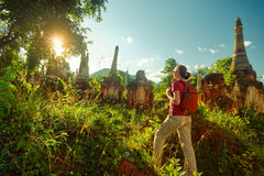 Backpacker traveling with backpack and looks at sunset among an