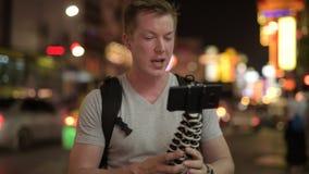 Backpacker turístico feliz joven del hombre vlogging con el teléfono en Chinatown en la noche almacen de video