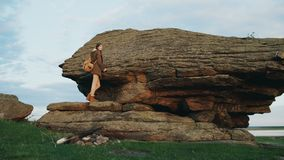 Backpacker turístico joven de la mujer que camina en roca en la puesta del sol Fotografía de archivo libre de regalías