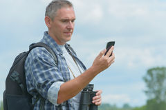 Backpacker using smart phone Stock Image