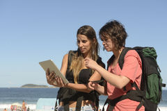 Backpacker using tablet as map Royalty Free Stock Images