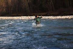 Backpacker waadt ruwe rivier Royalty-vrije Stock Afbeeldingen