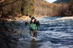 Backpacker wade rugged river Stock Photography