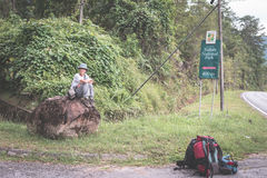 Backpacker waiting for hitchhike on the road for Kubah National Park, West Sarawak, Borneo, Malaysia. People traveling lifestyle. Desaturated and toned image Stock Photos