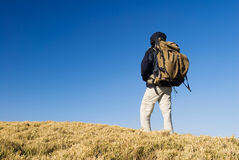 A backpacker walk on a yellow grassland in mountai Stock Photos