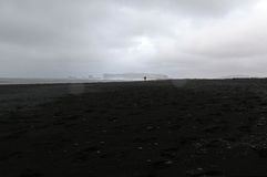 A Backpacker Walking on Black Sand Beach Royalty Free Stock Images