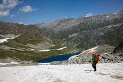 Backpacker walking down on a snow Royalty Free Stock Photos