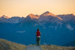 Backpacker walking on hiking trail in the mountain. Summer adventures summer vacation on the Alps. Wanderlust people traveling con. Cept Royalty Free Stock Photo