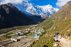 Backpacker walking mountain trail in Nepal. Royalty Free Stock Photo