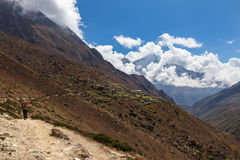 Backpacker walking mountain trail, Nepal village. Stock Images