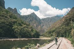 Backpacker walking on the railroad track to Machu Picchu, Peru, alternative to the usual tourist train connection. Machu Picchu ar. Cheological site top travel Royalty Free Stock Images