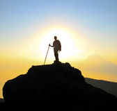 Backpacker with walking stick in sunset. A backpacker standing with walking stick on top of a mountain during sunset Royalty Free Stock Images