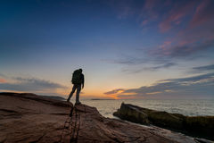 Backpacker watching a sunrise at Acadia National Park. This is a silhouette of a backpacker at Thunder Hole in Acadia National Park.  The man watches the Stock Photo