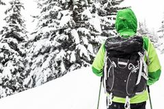 Backpacker on winter hike in white snowy woods royalty free stock photography