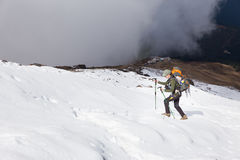 Backpacker woman ascending hiking walking snow mountain. Royalty Free Stock Photo