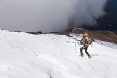Backpacker woman ascending hiking walking snow mountain. Young woman backpacker tourist walking hiking ascending difficult snow mountain slope, struggling Royalty Free Stock Photo