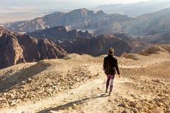 Backpacker woman descending hiking mountain ridge desert landscape. Backpacker tourist woman mountaineer walking hiking descending mountain ridge stone desert Royalty Free Stock Images