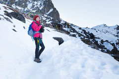 Backpacker woman standing snow mountain trail. Stock Photography
