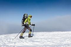 Backpacker woman is walking in winter mountains on sunny day.  Royalty Free Stock Photo