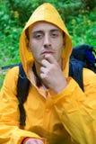 Backpacker in a yellow coat resting. Portrait of a backpacker in a yellow coat resting Stock Photography