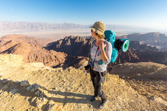 Backpacker young woman standing desert mountain edge canyon view Royalty Free Stock Photography
