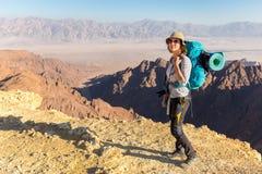 Backpacker young woman standing desert mountain edge canyon view Stock Photo