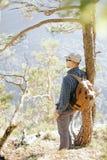Backpackermens die zich dichtbij de boom bevinden royalty-vrije stock foto