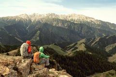 Backpackers женщин наслаждаются взглядом на скале горного пика Стоковые Изображения