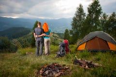 Backpackers пар стоят назад около лагерного костера и шатра Стоковое фото RF