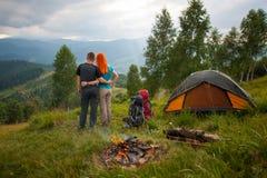 Backpackers пар стоят назад около лагерного костера и шатра Стоковые Фотографии RF