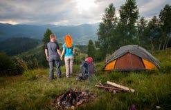 Backpackers пар стоят назад около лагерного костера и шатра Стоковая Фотография