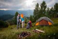 Backpackers пар стоят назад около лагерного костера и шатра Стоковые Изображения RF