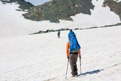 Backpackers проходят поле снега в скалистой горе в Altai mo Стоковое Фото