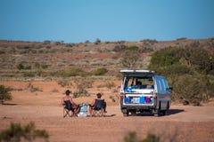 Backpackers с их белым campervan усаживанием в располагаясь лагерем стуле стоковые изображения